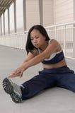 Junge asiatische Frau, die Fahrwerkbein-Muskeln ausdehnt Stockbild
