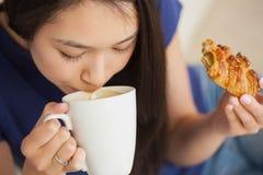 Junge asiatische Frau, die an ihrem Kaffee nippt und ein Gebäck hält Stockbild