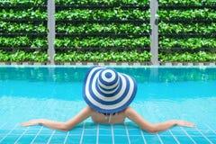 Junge asiatische Frau, die im Swimmingpool am Kurort sich entspannt Entspannendes Konzept Frauen sind am Poolside entspannend lizenzfreies stockbild