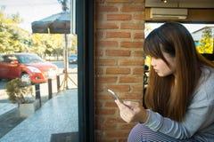 Junge asiatische Frau, die intelligentes Telefon im Shop, Geschäft technolog verwendet stockfoto