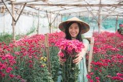 Junge asiatische Frau, die Kamillenblumen zeigt lizenzfreies stockfoto