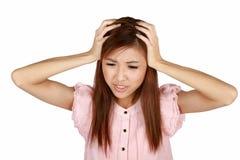 Junge asiatische Frau, die Kopfschmerzen hat. Stockfoto