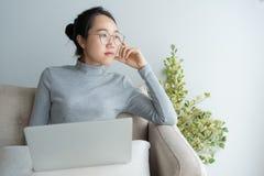 Junge asiatische Frau, die an Laptop im Haus und an stillstehendem Kinn des Sofas an Hand sitzen arbeitet lizenzfreie stockbilder