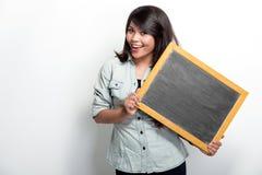 Junge asiatische Frau, die leeres schwarzes Brett hält Stockfotos