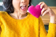 Junge asiatische Frau, die Luftkuß zu einem rosa Herzen macht stockfotos