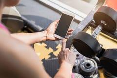 Junge asiatische Frau, die Smartphone in der Turnhalle verwendet lizenzfreie stockfotos