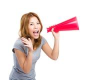 Junge asiatische Frau, die unter Verwendung des Megaphons zujubelt Lizenzfreie Stockfotos