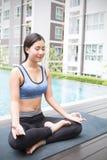 Junge asiatische Frau, die Yogabewegungen tut oder durch das Pool meditiert, lizenzfreie stockfotografie