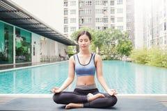 Junge asiatische Frau, die Yogabewegungen tut oder durch das Pool meditiert, lizenzfreie stockfotos