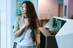Junge asiatische Frau im Büroholdingordner, lächelnd, Porträt stockfotografie