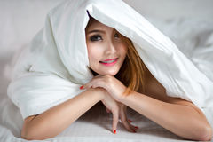 Junge asiatische Frau im Bett Stockbild