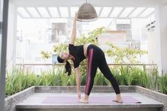 Junge asiatische Frau im Entspannung, das Position auf ihrem Balkonboden ausdehnt lizenzfreies stockfoto