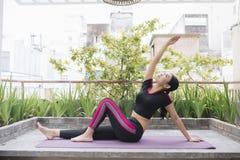 Junge asiatische Frau im Entspannung, das Position auf ihrem Balkonboden ausdehnt lizenzfreie stockbilder