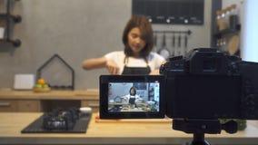 Junge asiatische Frau im Küchenaufnahmevideo auf Kamera Lächelnde asiatische Frau, die an Lebensmittel Bloggerkonzept arbeitet