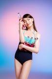 Junge asiatische Frau mit den geschlossenen Augen, die im Badeanzug hält Flaschen mit Auffrischungssommer aufwerfen, trinkt Stockfotos
