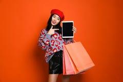 Junge asiatische Frau mit Einkaufstaschen auf Farbhintergrund stockfotos