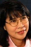 Junge asiatische Frau mit Gläsern lizenzfreie stockbilder