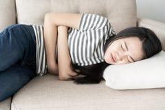Junge asiatische Frau sitzen auf Sofa im Wohnzimmer, die Frauen, die schmerzliche Magenschmerzen haben stockfoto