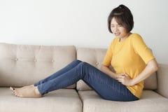 Junge asiatische Frau sitzen auf Sofa im Wohnzimmer sie schmerzliche Magenschmerzen habend stockbilder