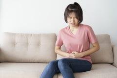 Junge asiatische Frau sitzen auf Sofa im Wohnzimmer sie schmerzliche Magenschmerzen habend lizenzfreie stockfotografie
