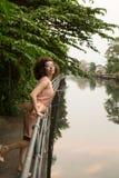 Junge asiatische Frau steht auf dem Damm des Flusses gehen Stockfoto