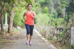 Junge asiatische Frau, welche die Übung im Freien in einem Park, rüttelnd tut stockfotos