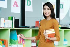 Junge asiatische Frau, welche die Bücher stehen am Bibliothekshintergrund hält, lizenzfreie stockfotografie