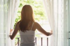 Junge asiatische Frauenöffnungsvorhänge morgens lizenzfreie stockfotografie