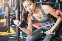 Junge asiatische Frauen, die Dummkopf in der Sportturnhalle anheben lizenzfreies stockbild