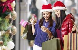 Junge asiatische Frauen, die Mobiltelefon während des Weihnachtseinkaufens verwenden stockfotos