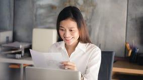 Junge asiatische Geschäftsfrau, die am Arbeitsplatz lächelt und pape liest stockfoto