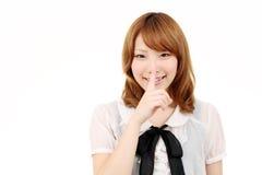 Junge asiatische Geschäftsfrau, die Finger zu den Lippen setzt Stockfoto