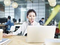 Junge asiatische Geschäftsfrau, die im Büro arbeitet lizenzfreie stockfotos