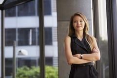 Junge asiatische Geschäftsfrau, die zur Kamera, Arme gekreuzt schaut stockfoto