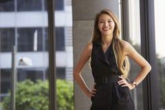 Junge asiatische Geschäftsfrau, die zur Kamera, Hände auf Hüften schaut lizenzfreies stockfoto