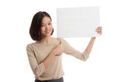 Junge asiatische Geschäftsfraushow greift oben mit weißem leerem Zeichen ab Lizenzfreies Stockbild