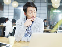Junge asiatische Geschäftsperson, die stark im Büro denkt Lizenzfreie Stockbilder