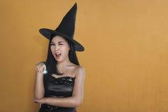 Junge asiatische Hexenfrau im Hut unter Verwendung des magischen Bannes Stockbilder