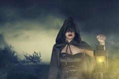 Junge asiatische Hexenfrau im schwarzen Korsett und im Mantel mit Kapuze mit La Stockfotos