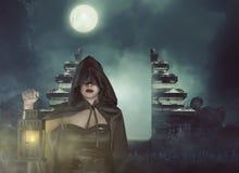 Junge asiatische Hexenfrau im schwarzen Korsett und im Mantel mit Kapuze mit La Lizenzfreie Stockfotografie