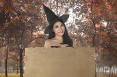Junge asiatische Hexenfrau mit dem Hut, der Fahne hält Stockbilder