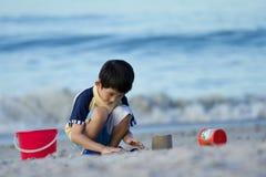 Junge asiatische Jungenspiele am Strand lizenzfreies stockbild