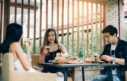 Junge asiatische Leute, die Spaß am Trinken mit dem Zujubeln mit Bier am Restaurant haben stockfotografie