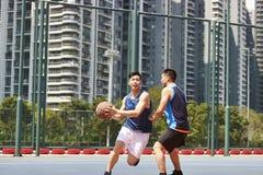 Junge asiatische Männer, die Basketball spielen stockbilder