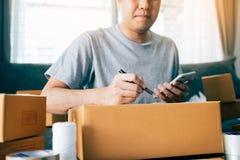 Junge asiatische Manngeschäftseigentümerhände, die Adresse auf Pappschachtel im Arbeitsplatz- oder Innenministerium schreiben lizenzfreie stockfotografie