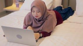 Junge asiatische moslemische Frau, die auf Bett unter Verwendung des Laptops niederlegt stock video