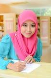 Junge asiatische moslemische Frau im beschäftigten Studieren des Kopftuchlächelns Stockfotografie