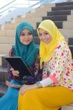 Junge asiatische moslemische Frau im Kopftuch lächeln zusammen Lizenzfreies Stockfoto