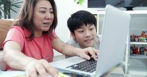 Junge asiatische Mutter, die an der Laptop-Computer mit seinem Sohn mit Lächelngesicht arbeitet stock footage