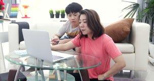 Junge asiatische Mutter, die an der Laptop-Computer mit seinem Sohn mit Lächelngesicht arbeitet stock video